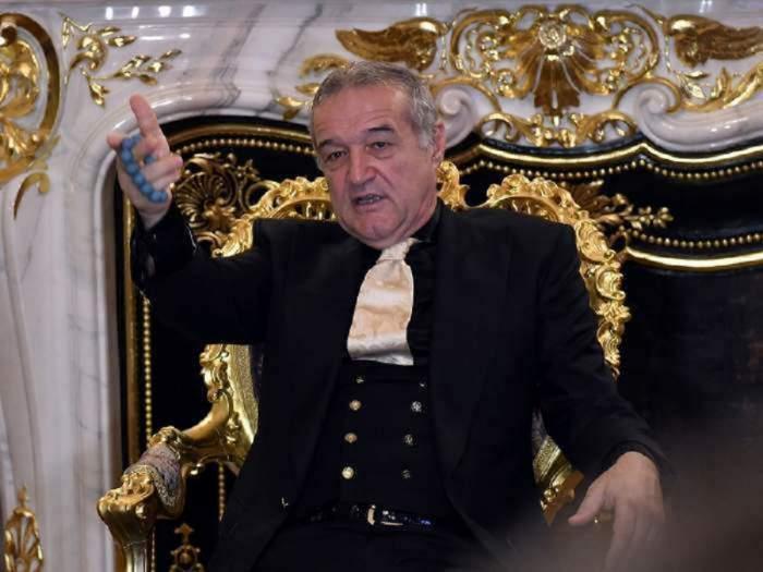 Gigi Becali stă pe scaun. Patronul FCSB e îmbrăcat într-un costum negru și gesticulează.
