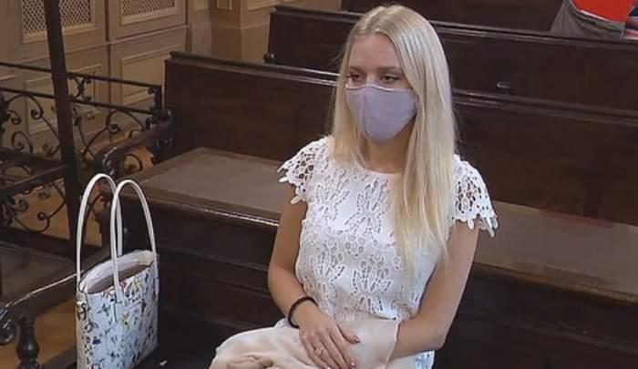 Julija Adlesic, tânăra care și-a tăiat mâna pentru asigurare, în sala de judecată, cu mască și o rochie albă