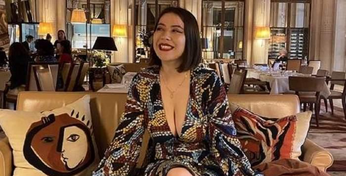 Jeanne, tânăra cu decolteul generos, râzând pe o canapea, îmbrăcată cu o rochie aurie