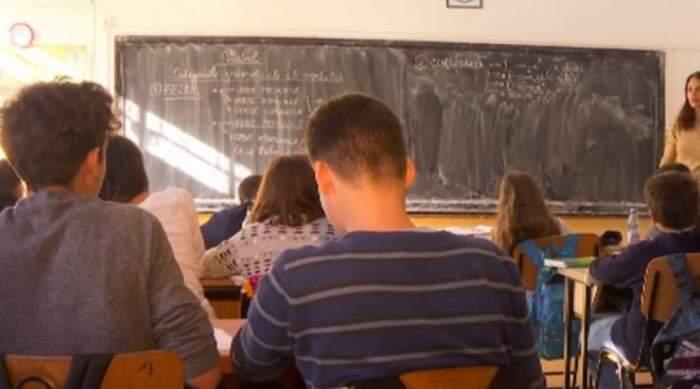 elevi la şcoală aşezaţi în bănci