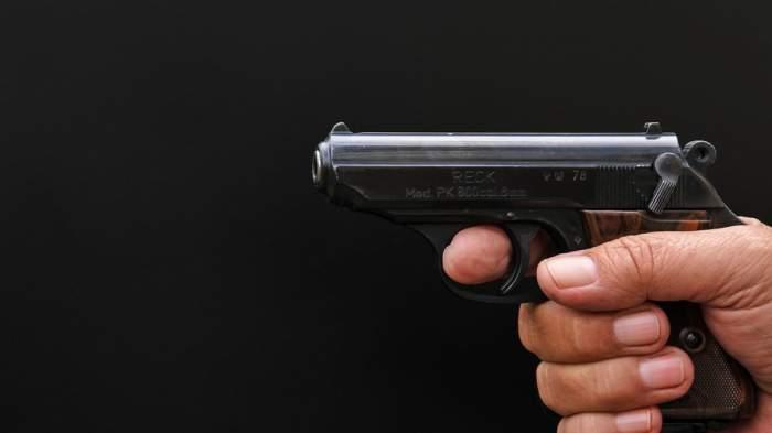 mână care ţine un pistol pe fundal negru