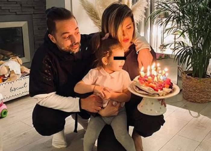 Anamaria Ionescu și Tudor Ionescu își țin fiica în brațe. Cei doi se uită la un tort cu lumânări aprinse.