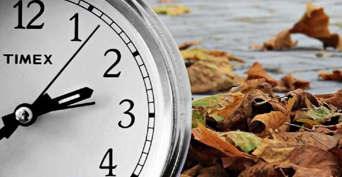 Un ceas aflat pe un fundal de frunze portocalii căzute toamna