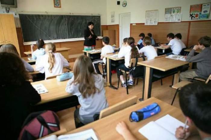 Fotografie cu mai mulți elevi și profesoara lor, în sala de curs