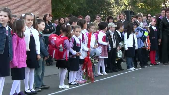 Prima zi de școală. Copii așteptand în careu cu flori