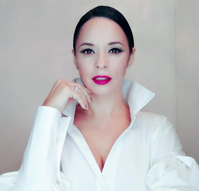 Andreea Marin, foarte senzuală, îmbrăcată într-o cămașă albă, foarte decoltată.