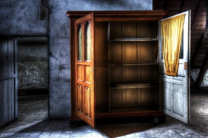Poză editată cu un dulap gol cu ușile deschise, într-o casă abandonată