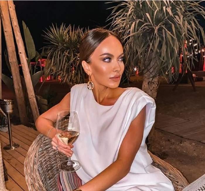 Monica Orlanda la o terasă, poartă o bluză albă și bea vin