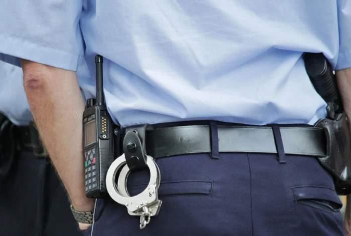 Spatele unui polițist. Acesta e îmbrăcat în uniformă și are mâna în buzunar.