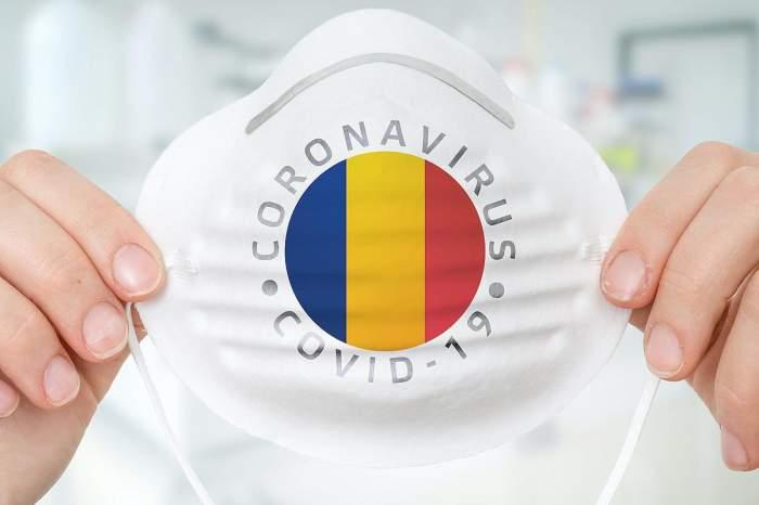 O persoană ține o mască de protecție cu steagul României