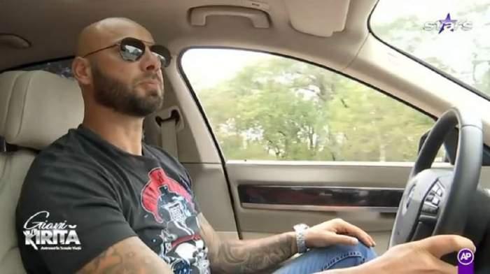 Giani Kiriță la volan. Fostul sportiv poartă ochelari de soare și un tricou negru.