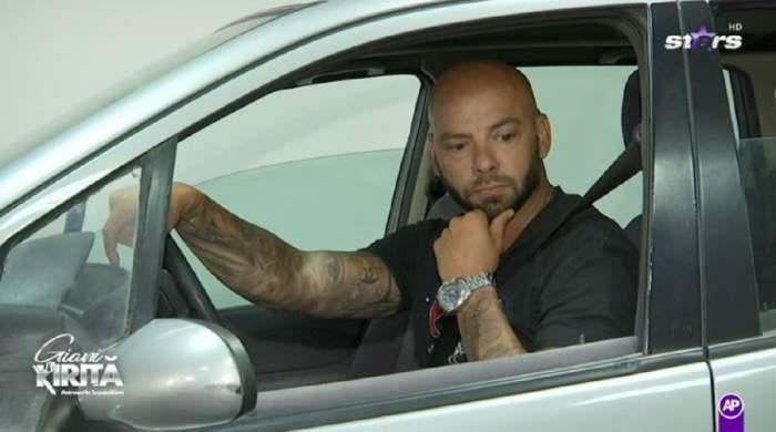 Giani Kiriță la volanul unei mașini. Sportivul e îmbrăcat într-un tricou negru, ține mâna pe volan și poartă un ceas.