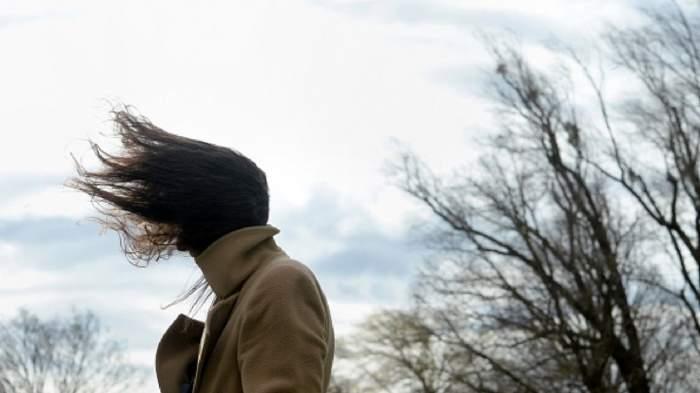 Femeie în haină maro, cu părul suflat de vânt puternic