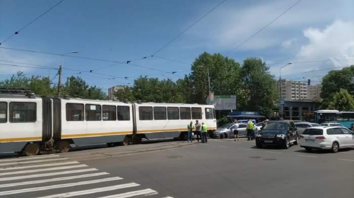 Tramvai din București în intersecție, mașini și oameni în veste reflectorizante