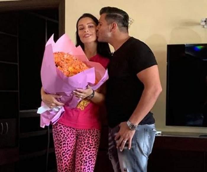 Florin Pastramă o sărută pe obraz pe Brigitte. Afacerista ține în mână un buchet mare de flori.