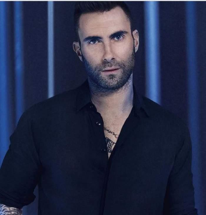 Adam Levine poartă o cămașă neagră și se uită serios la cameră