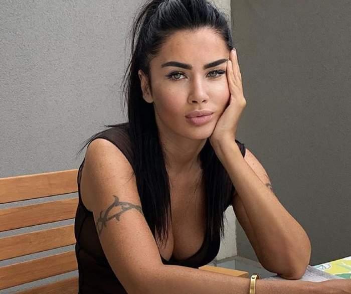 Oana Zăvoranu stă pe un scaun de lemn, isi sprijina capul in pal,a si are părul prins