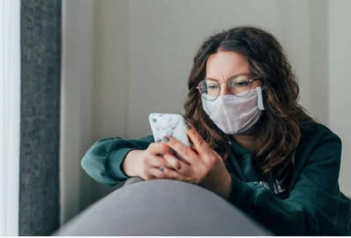 Imagine ilustrativa cu o femeie care poarta ochelari si masca de protectie pe fata, in timp ce se uita pe telefon