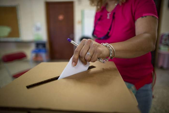 Femeie în tricou roz introduce vot în urnă la alegerile din Puerto Rico