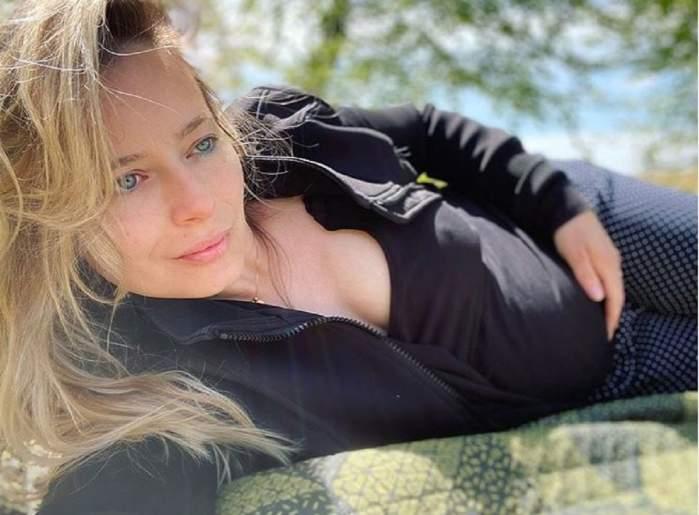 Laura cosoi stă întinsă pe o pătură. Vedeta își ține mâna pe burtică