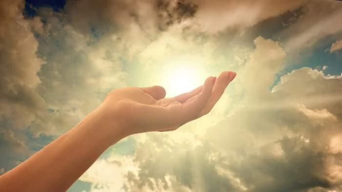 Mână întinsă spre un cer albastru cu lumină după nori