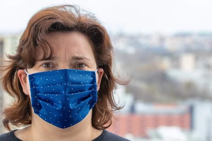 Femeie cu mască albastră, protejată de COVID