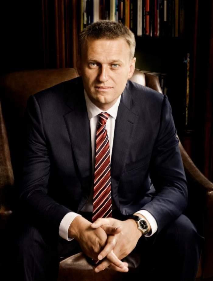 Aleksei Navalnii sta pe scaun, aplecat in fata, poarta costum negru si cravata grena