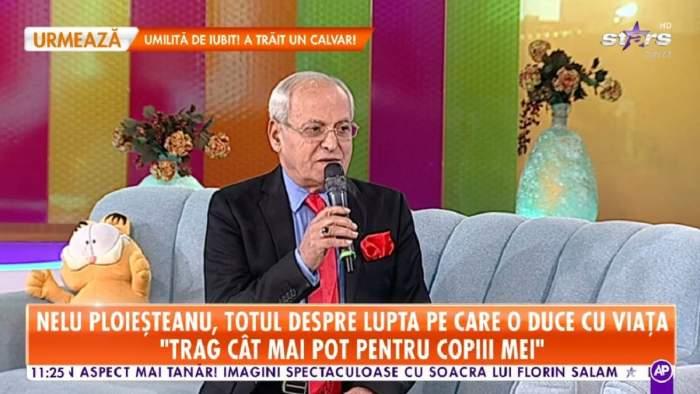 Nelu Ploieșteanu pe canapeaua de la Antena Stars. Artistul poartă un costum negru și o cravată roșie
