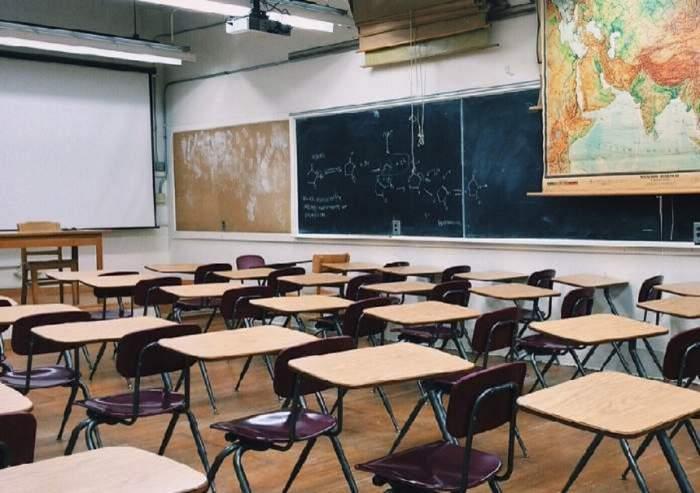 O clasă cu scaune și bănci. În dreptul tablelor se află o hartă.
