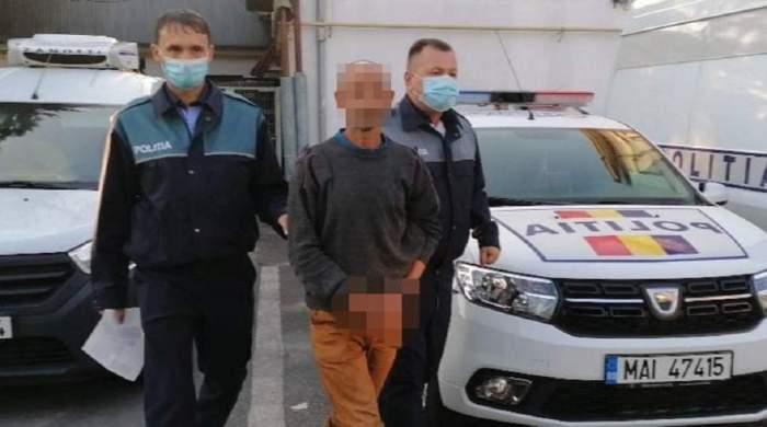 În poză sunt doi polițiști care-l țin de brațe pe tatăl care și-a abuzat minora. În spate sunt două mașini de Poliție.