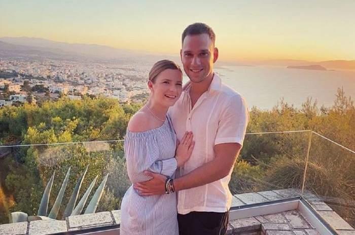 Cristina Ciobănașu și Vlad Gherman pe balcon. Cei doi se țin în brațe. Actrița poartă o rochie în dungi, iar el o cămașă roz.