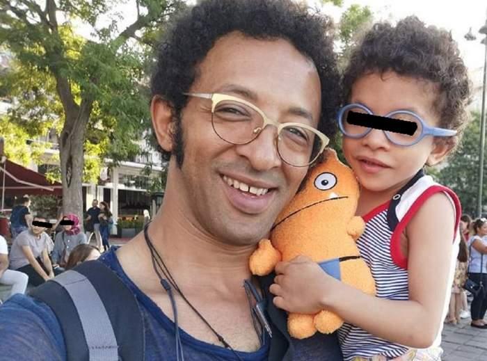Kamara și Leon poartă ochelari de vedere. Cei doi zâmbesc, iar fiul artistului ține în brațe o jucărie