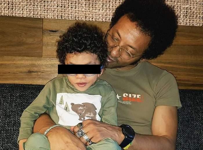 Kamara și fiul lui stau pe un pat de spital. Cei doi zâmbesc larg