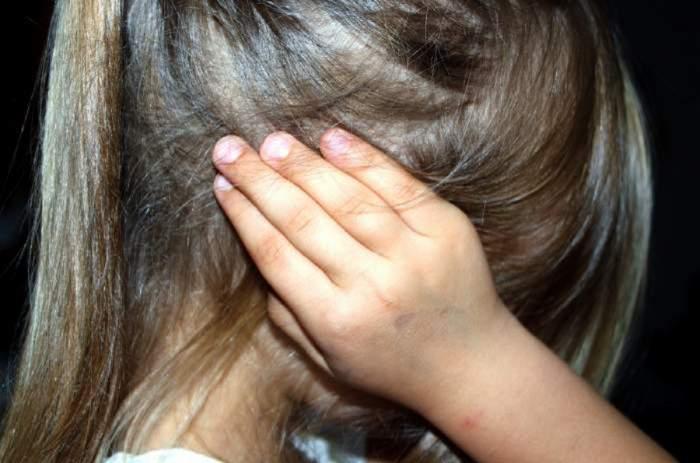 Imagine ilustrativă cu o fetiță atacată, cu mâinile la urechi