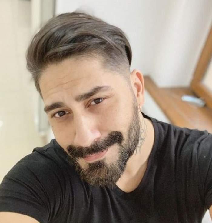 Fotografie cu celebrul Connect-R, zâmbitor, îmbrăcat în tricou negru