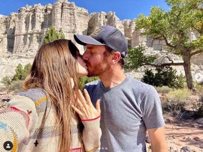 Lily Collins si iubitul ei se saruta, in timp ce ea arata inelul de logodna de pe deget