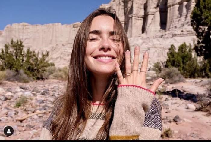 Lily Collins zambeste si arata inelul de logodna de pe deget