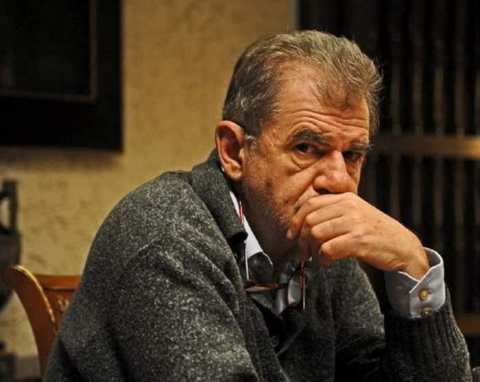 Florin Zamfirescu stă pe scaun. Actorul e îmbrăcat în pulover gri și ține mâna la gură.