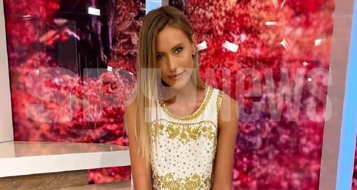 Gabriela Prisăcariu cu un top alb cu auriu și cu flori roz în fundal