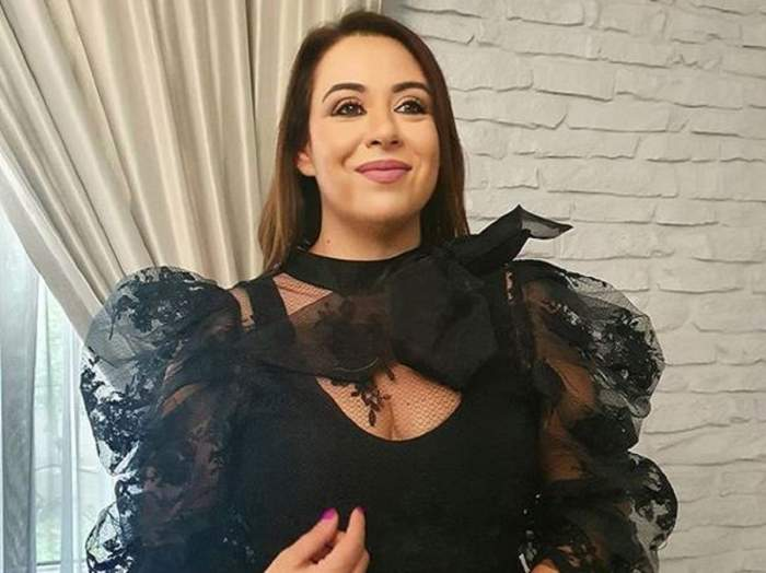 Oana Roman poartă o bluză neagră, transparentă. Vedeta privește într-o parte.