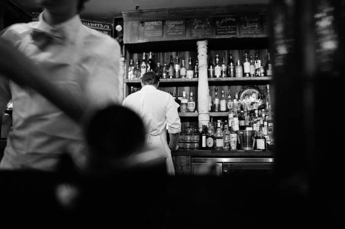 Imagine alb negru cu barmani și oameni într-un bar