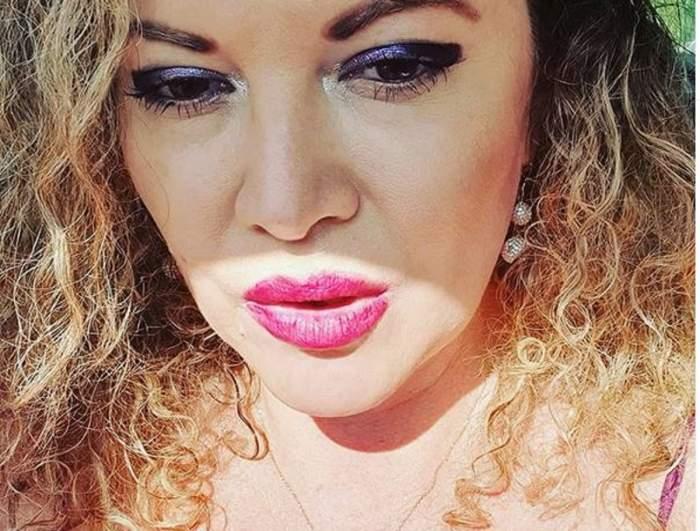 Oana Lis poartă un maiou roz și e dată cu un ruj pe buze în aceeași nuanță. La ochi e machiată cu mov.