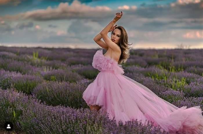 Monica Orlanda poarta o rochie voluminoasa roz, intr-un camp cu lavanda