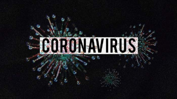 Virus pe fundal negru pe care scrie coronavirus