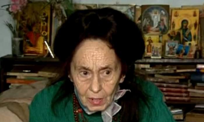 Adriana Iliescu, îmbrăcată în verde, în locuința ei, înconjurată de icoane