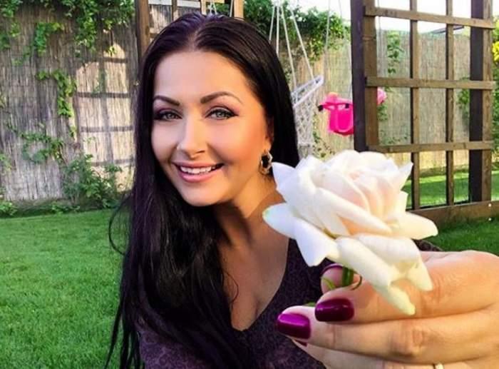 Gabriela Cristea este în curtea casei sale. Vedeta are în mână o floare și zâmbește.