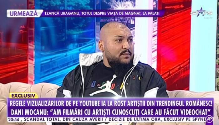 Dani Mocanu stă pe canapea. Artistul poartă un trening negru.