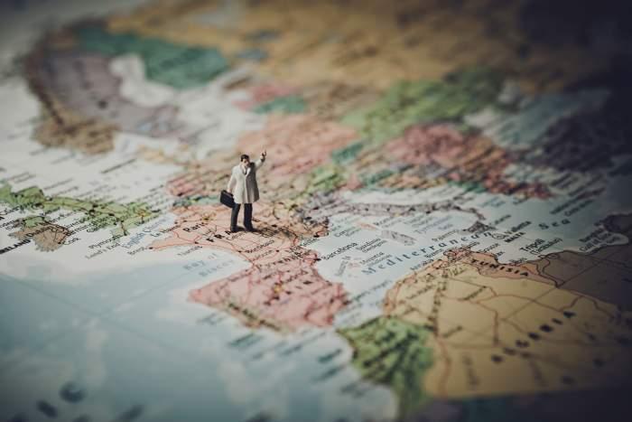 imagine ilustrativă cu harta lumii, în mijlocul căreia se află un băbat cu o geantă în mână