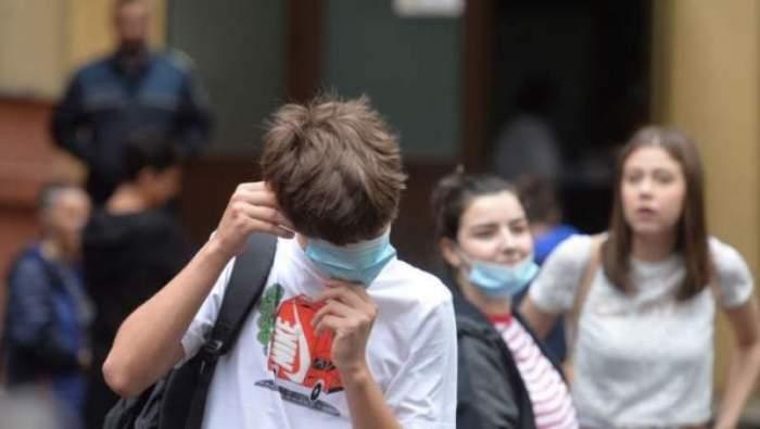 Mai mulți copii cu măști, însă în prim-plan apare un băiat aranjându-și masca de protecție pe față