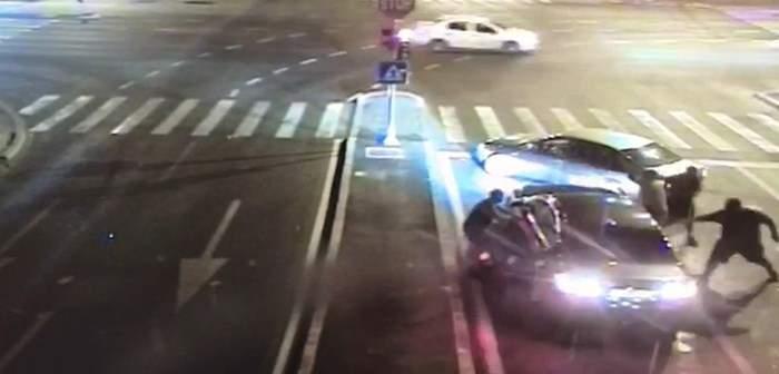 Fotografie de la fața locului, undemai muți romi sar cu parii pe o mașină oprită la semafor